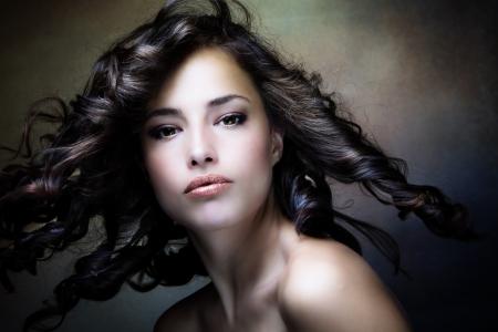 sinnliche Brünette Frau mit glänzenden curly seidiges Haar in Bewegung studio shot Standard-Bild