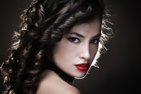 sensual young woman with shiny curly hair and red lips portrait in studio