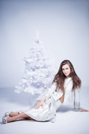 smiling beautiful brunette woman in silver dress sit by the christmas tree Stock Photo - 16546362