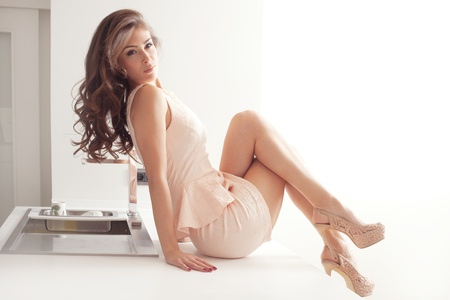 short dress: beautiful elegant woman in short pink dress and high heels sit on bar in the modern kitchen