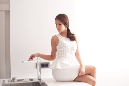 young woman in elegant white dress in modern kitchen Stock Photo - 16847800
