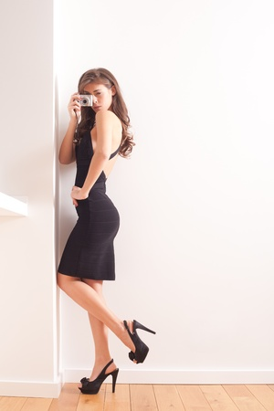 young elegant woman with compact camera full body shot indoor Stock Photo - 16847795