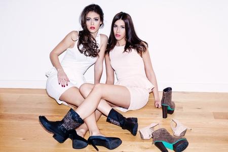 par de mujeres j�venes con un mont�n de zapatos en el piso Foto de archivo - 16847790
