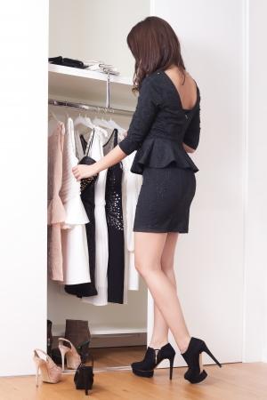 junge elegante Frau vor offenem Schrank voller elegante Kleider wählen, was Ganzkörperfoto tragen
