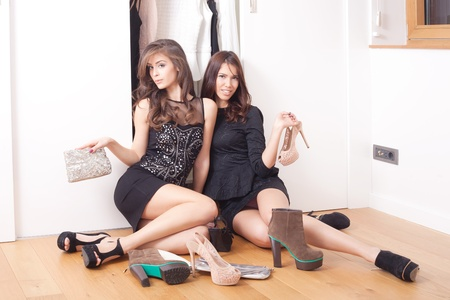 couple of young women in elegant dresses sit in front closet with shoes in front of them Stock Photo - 17014776