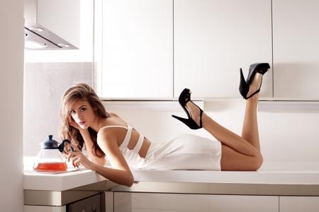 stilvolle junge Frau im weißen Kleid in der modernen weißen Küche indoor shot