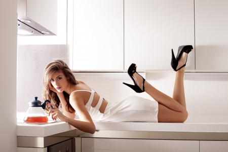 indoor shot: stylish young woman in white dress in modern white kitchen indoor shot