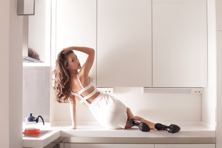 stylish young woman in white dress in modern white kitchen indoor shot