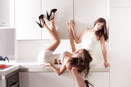stylish young women in white dresses in modern white kitchen indoor shot Stock Photo - 17049496