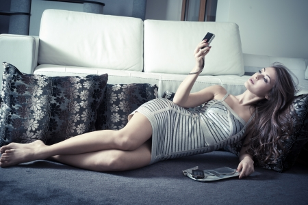 sexy pictures: elegant young voman in living room lie on carpet take picture of herself  with digital camera Stock Photo