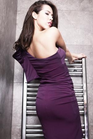 beautiful brunette girl in elegant purple dress in bathroom Stock Photo - 17049483