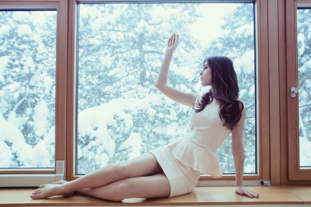 young woman in elegant short dress barefoot sit by window looking at winter snow day Stock Photo - 17255283