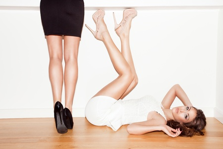couple of young women in elegant dresses and high heel shoes indoor shot Stock Photo - 17255284