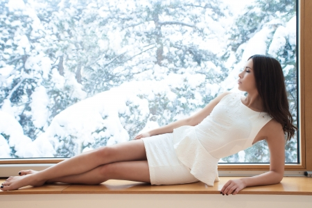young woman in elegant short dress barefoot sit by window looking at winter snow day Stock Photo - 17500733