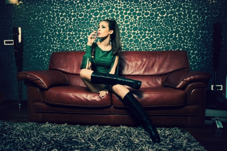 attractive young woman in green dress and long boots sit and smoke in retro style living room  photo