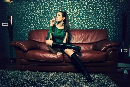 attraktive junge Frau im grünen Kleid und lange Stiefel sitzen und im Retro-Stil Wohnzimmer rauchen