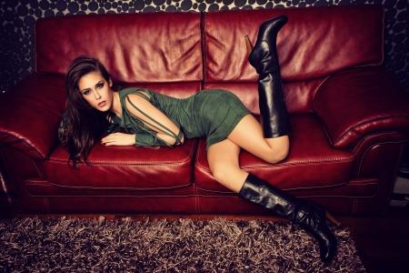 leren bank: jonge mode vrouwelijk model in korte groene jurk en hoge hak laarzen pose op rood lederen sofa