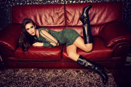 young fashion female model in short green dress and high heel boots pose on red leather sofa