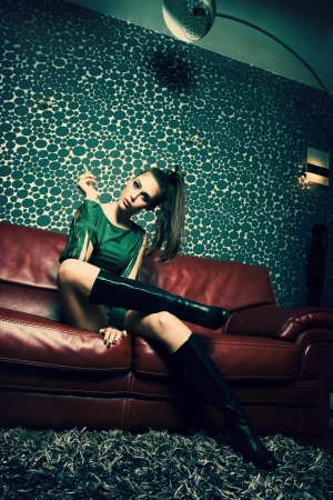 attractive young woman in green dress and long boots sit and smoke in retro style living room Stock Photo - 17577029