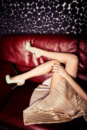 weibliche Beine in eleganten Schuhen mit hohen Absätzen und goldenen Kleid auf Ledersofa Standard-Bild