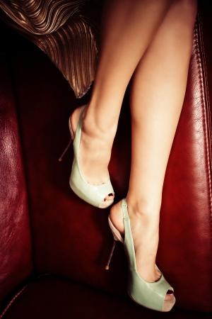 leren bank: vrouwelijke benen in elegante hoge hak schoenen op leren bank Stockfoto