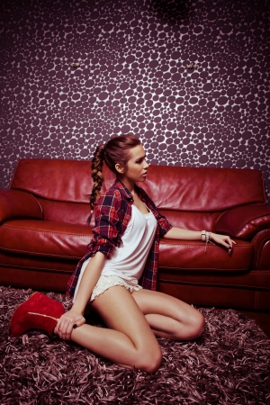 young fashion girl in modern living room sit on carpet lean on leather sofa photo