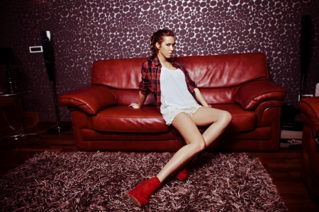 young fashion girl in modern living room sit on leather sofa Stock Photo - 17560493