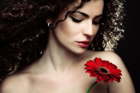 cabello rizado: pelo rizado mujer joven Retrato de la belleza con la flor Foto de archivo