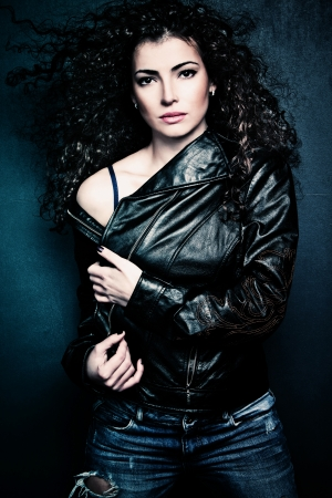 curly hair beautiful young woman wearing black leather jacket and blue jeans, studio shot photo