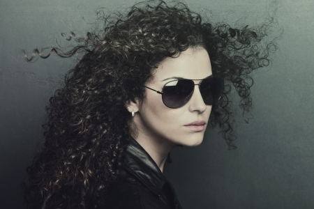 curly hair  young woman with sunglasses studio shot photo