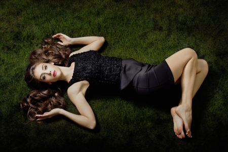 beautiful young elegant barefoot woman  lie on grass, small amount of grain added  photo