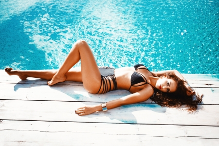 beautiful brunette young woman in bikini relax by pool summer day photo