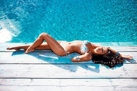female body: beautiful young woman in bikini lie by the pool summer day
