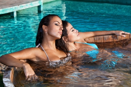young women relaxing in outdoor pool summer day photo