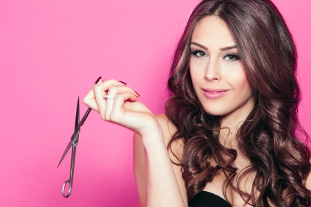 beautiful hair: close up of a smiling young woman with beautiful hair, hold scissors in one hand pink background