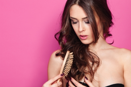 hair brush: beautiful young woman brush hair studio shot pink background