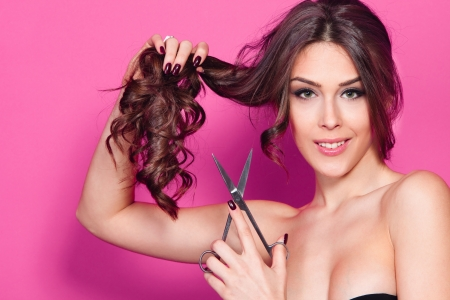young woman hold scissors studio shot pink background