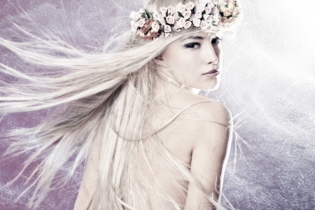 beautiful young woman with long blond flying hair and wreath of flowers
