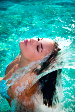 attractive young woman refresh in pool under the small waterfall photo