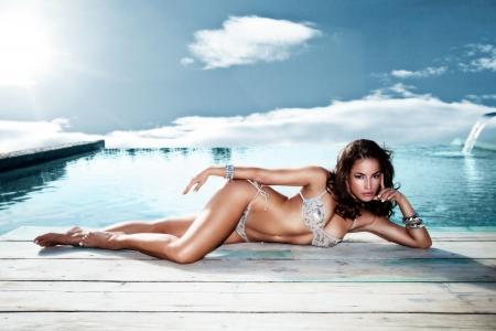 schöne Frau am Pool entspannen Himmel mit Sonne und Wolken im Hintergrund