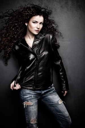 attractive long hair young woman in black leather jacket and blue jeans studio shot small amount of grain added photo