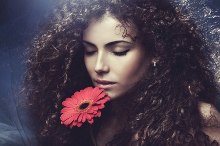 curly hair woman: curly hair  young woman beauty portrait with flower