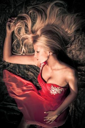 sensual blond woman in red dress studio shot photo