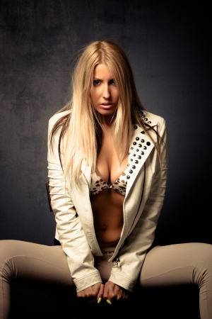 sexy blond woman in leather jacket studio shot photo