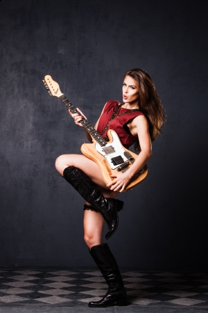sexy guitar: rock girl in motion with electric guitar  studio shot