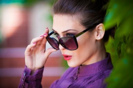 elegante junge Frau mit Sonnenbrille im Freien erschossen