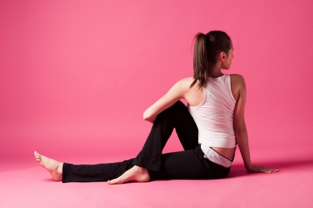 pratice: young woman doing spinal extension exercise studio shot pink background