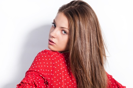 long red hair woman: young woman in red  shirt look back studio shot