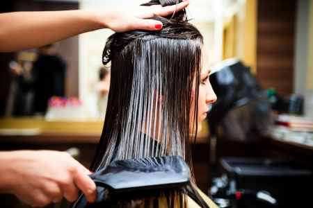 hair treatment: young woman at hairdresser Stock Photo