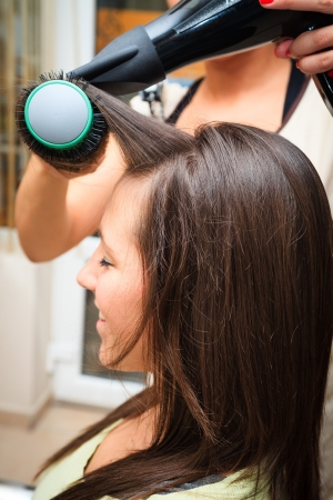 hair dryer: young woman at hairdresser do hairstyling Stock Photo